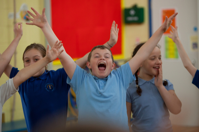 PPA Cover in Primary School - child raising their hands in joy