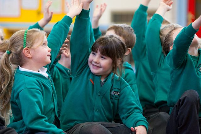 PPA Cover in Primary Schools: children raising their hands